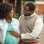 Smiling African American pregnant couple